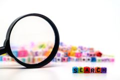 Word `SEARCH` on the magnifying glass with alphabet letter beads background stock photos