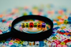 Word `SEARCH` on the magnifying glass. With alphabet letter beads background, Search engine optimization concept added color filter Stock Photos