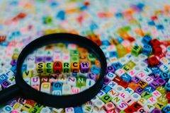 Word `SEARCH` on the magnifying glass. With alphabet letter beads background, Search engine optimization concept added color filter Royalty Free Stock Photography