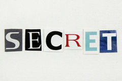 Word secret cut from newspaper on white paper Stock Image
