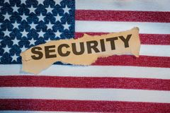 The word security in torn paper laying on the American Flag Stock Images