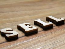 The word sell. Wooden word, `sell` inscription on a wooden background Royalty Free Stock Photo