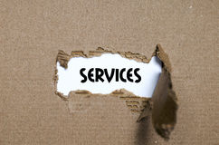 The word services appearing behind torn paper Stock Images