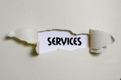 The word services appearing behind torn paper Royalty Free Stock Photo