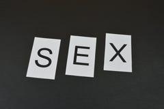 Word `Sex` on black background Stock Photos