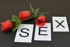 Word `Sex` and red rose on black background. Plus roses Stock Photos