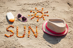 Word and shape of sun, sunglasses, sun lotion and straw hat on sand at beach, summer time Royalty Free Stock Photography