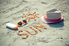 Word and shape of sun, sunglasses, sun lotion and straw hat on sand at beach, summer time Royalty Free Stock Image