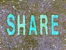 The word SHARE on the floor in a kids park. The word SHARE stencilled in turquoise and green letters onto the floor made out of wet pour rubber surface material royalty free stock image