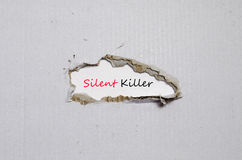 The word silent killer appearing behind torn paper. The word silent killer behind torn paper royalty free stock photo
