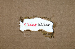 The word silent killer appearing behind torn paper. The word silent killer behind torn paper Royalty Free Stock Image