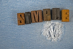 Word simple in wooden letterpress type on denim Royalty Free Stock Photography