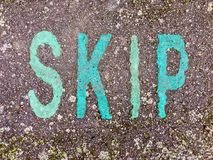 The word SKIP on the floor in a kids park. The word SKIP stencilled in green and pink letters onto the floor made out of wet pour rubber surface material in a royalty free stock images