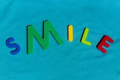 The word Smile composed from letters. The word Smile composed from colorful children toy big letters on the grass stock photography