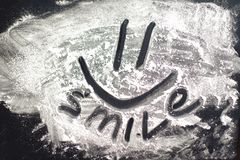 Smile Inscription. Word smile written and emoji on white flour. Inscription smile with emoji on white culinary flour on dark board royalty free stock photos