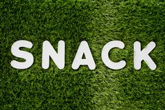 Word SNACK white wooden alphabet on gree grass background textur Royalty Free Stock Image