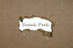 The word sneak peek appearing behind torn paper. Stock Photography