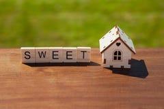 Word snoepje van houten brieven en klein stuk speelgoed blokhuis op bruine oppervlakte, groen gras op achtergrond Concepten zoet  royalty-vrije stock foto's