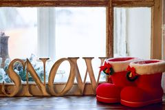 Word SNOW - wooden letters and red with white border and handbell Christmas boots on windowsill stock images