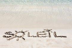 Word SOLEIL écrit sur le sable sur une belle plage, avec les vagues bleues à l'arrière-plan image libre de droits