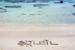 Word SOLEIL écrit sur le sable sur une belle plage, avec les vagues bleues à l'arrière-plan images libres de droits