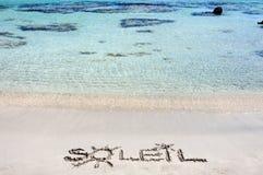 Word SOLEIL écrit sur le sable sur une belle plage, avec les vagues bleues à l'arrière-plan images stock