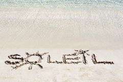 The Word SOLEIL Written on Sand on a beautiful beach, with blue waves in background Royalty Free Stock Image