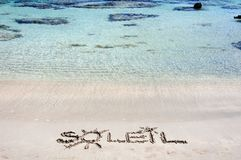 The Word SOLEIL Written on Sand on a beautiful beach, with blue waves in background Royalty Free Stock Images