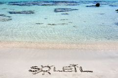 The Word SOLEIL Written on Sand on a beautiful beach, with blue waves in background Stock Images