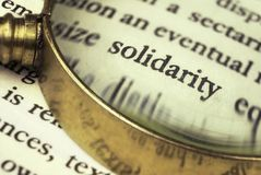 The word `solidarity` emphasized by a magnifying glass. stock photos
