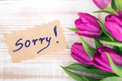 Word SORRY and bouquet of tulips. On wooden background Royalty Free Stock Photography