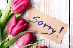 Word SORRY and bouquet of tulips. On wooden background Royalty Free Stock Photos