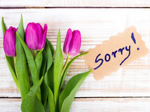 Word SORRY and bouquet of tulips on wooden background Royalty Free Stock Images