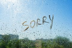 Word sorry on the window with raindrops. Background drop of water on the glass, blue sky, sun, city. Word sorry on the window with raindrops. Background drop of royalty free stock images