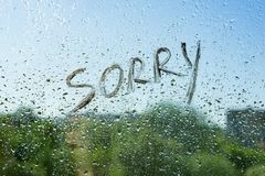 Word sorry on the window with raindrops. Background drop of water on the glass, blue sky, sun, city.  royalty free stock photo