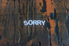 The word sorry written in white block letters. On a orange and brown wood surface royalty free stock photos