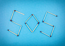 Word SOS made of matchsticks. Isolated on blue background Stock Photo