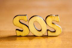 The word `sos` made of wooden letters. Wood inscription on table Stock Images