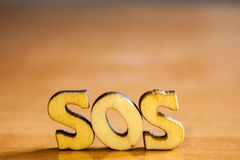 The word `sos` made of wooden letters. Wood inscription on table royalty free stock image