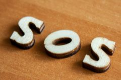 The word `sos` made of wooden letters. Wood inscription on table stock photos