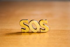 The word `sos` made of wooden letters. Wood inscription on table Royalty Free Stock Images