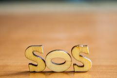 The word `sos` made of wooden letters stock photography