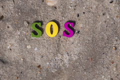 Word sos from wooden letters. On a sandy beach, a top view Royalty Free Stock Images