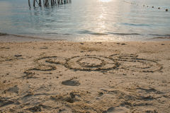 "Word "" SOS "" Write in sand on the beach.  Royalty Free Stock Photography"