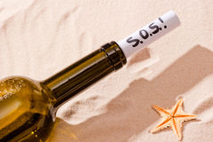 Word SOS is written in note in the bottle Royalty Free Stock Images