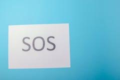 Word SOS written on paper Royalty Free Stock Photos