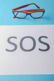 Word SOS written on paper Stock Image