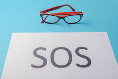 Word SOS written on paper Stock Photography