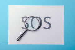 Word SOS written on paper Stock Photo
