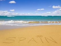 The word Spain written on the beach sand Stock Image